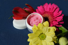 Pink cream, lips balm. A small dose with strawberry cream surrounded by flowers Royalty Free Stock Images