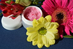 Pink cream, lips balm. A small dose with strawberry cream surrounded by flowers Stock Photos