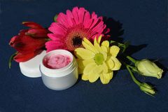 Pink cream, lips balm. A small dose with strawberry cream surrounded by flowers Stock Images