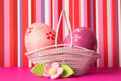 Pink and crimson Easter eggs in a basket with pink flower Royalty Free Stock Image