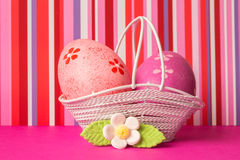 Pink and crimson Easter eggs in a basket with white flower Royalty Free Stock Images