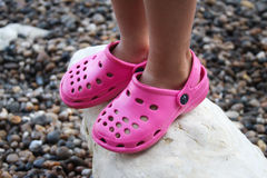 Pink croc shoes. Close-up of pink crocs shoes on the beach Stock Photos