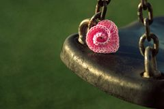 Pink crocheted spiral heart lies on swing on green background. stock photos