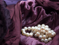 Pink cultured pearls on burgundy velvet crumpled dress backgroun. Close up image of pink cultured pearls on a crinkled burgundy satin and velvet crumpled dress Stock Images