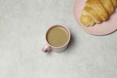 The cup of coffee and  croissant  on the granite background stock photography