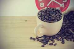 Pink cup with coffee grain and a red alarm clock. Image vintage style Stock Photos