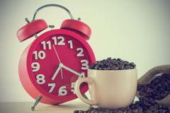 Pink cup with coffee grain and a red alarm clock. Image vintage style Royalty Free Stock Images