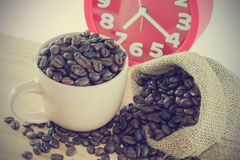 Pink cup with coffee grain and a red alarm clock. Pink cup with coffee grain in to and a red alarm clock. Image vintage style Stock Images