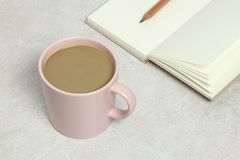 The pink cup of coffee, opened book and pencil on the granite texture stock photo