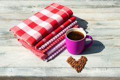 Pink cup of hot black coffee with roasted coffee beans as hear. T together with a Stack of red white checkered and striped linen tableclothes on rustic bright Stock Image