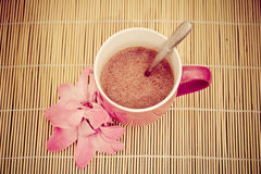 Pink cup of hot chocolate on bamboo tablecloth Royalty Free Stock Images
