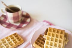 Pink cup of tea and Brussel waffles on white table royalty free stock image