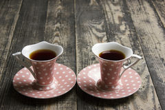 Pink cup of tea. Two pink cup of tea on a wooden background. Space for text Stock Photography