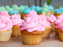 Pink cupcake. Up close with lots of cupcakes in background Royalty Free Stock Image
