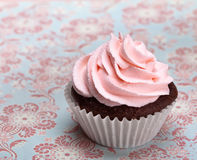 Pink Cupcake. A cute chocolate cupcake with pink icing and copy space stock photos