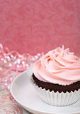 Pink Cupcake. A cute chocolate cupcake with pink icing and copy space royalty free stock photo