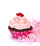 Pink Cupcake. A chocolate cupcake with heart sprinkles and pink icing on a white background with ribbons. Copy space royalty free stock photo