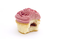 Pink cupcake with bite taken Stock Image
