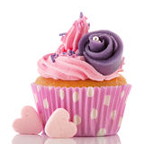 Pink cupcake with buttercream. Pink buttercream on cupcake with candy hearts and purple flower stock images