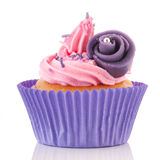 Pink cupcake with buttercream. Pink buttercream on cupcake with sprinklets and purple flower Stock Photos