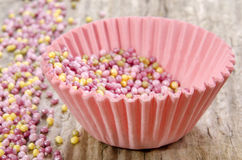 Pink cupcake case with sugar sprinkles Stock Images