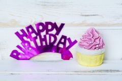 Pink Cupcake and Happy Birthday Text. Pink Cupcake and Happy birthday purple sign for greeting cards royalty free stock photography
