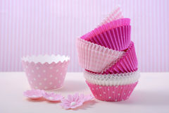 Pink cupcake paper cups. On a white wood table with pink candy stripe background Royalty Free Stock Images