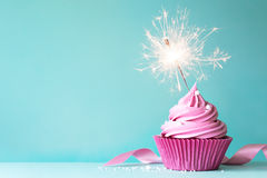 Pink cupcake with sparkler. Cupcake with pink buttercream and sparkler stock photos
