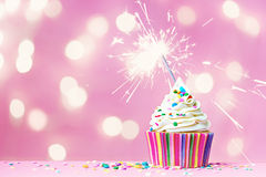 Pink cupcake with sparkler. And fairy lights Stock Photography