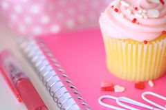 A pink cupcake with sprinkles, a pink notebook, paperclips and a pen. A white desktop with a pink cupcake, notebook, a pen, paperclips and a dotted pink ribbon Stock Photography