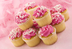 Pink Cupcakes. A stack of pink cupcakes with white sprinkles and pink background, horizontal with copy space Royalty Free Stock Image