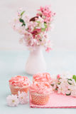 Pink cupcakes. Pink butter cream cupcakes and cherry blossoms stock photography