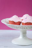 Pink cupcakes with cream cheese frosting on cake plate Stock Image