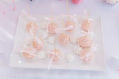 Pink cupcakes with the golden drops and ribbons. On the white plate Stock Photo