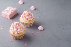 Pink cupcakes with heart shaped candy for Valentines Day. Pink cupcakes with heart shaped candy and gift box for Valentines Day or wedding stock image