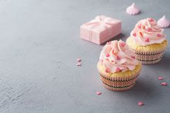 Pink cupcakes with heart shaped candy for Valentines Day. Pink cupcakes with heart shaped candy. Valentines Day or wedding treats concept. Copy space stock photography