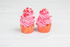 Pink cupcakes with hearts on white wooden background Stock Photos