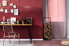 Pink woman`s workspace interior. Pink curtain and logs of wood next to a desk with clock and metal chair in woman`s workspace interior Stock Image
