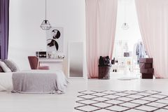 Pink curtains in sophisticated bedroom. Pastel pink curtains in sophisticated bedroom with dressing table and walk-in closet Stock Photo