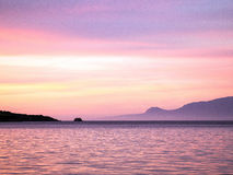 Pink Dawn Light. Reflected in water and clouds, Gulf of Corinth, Greece, view to Peloponnese mountains Stock Photo
