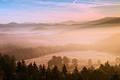 Pink daybreak in hilly landcape. Autumn freeze misty morning in a beautiful hills. Peaks of hills are sticking out from pink orang Royalty Free Stock Photo