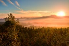 Pink daybreak in landscape. Autumn freeze misty morning in a beautiful hills. Peaks of hills are sticking out from pink orang Stock Photos