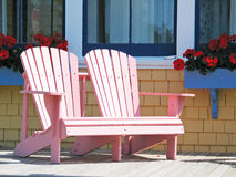 Pink Deck Chairs. Double pink Adirondack chair sitting on the sunny deck with flowering geraniums in the background stock photo