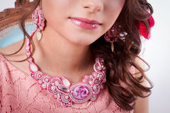 Pink decoration technique soutache a girl. In a pink dress, earrings and necklaces Stock Image