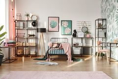 Pink decorations in botanical bedroom. Pastel pink and emerald green decorations and textiles in botanical bedroom interior with scandinavian style furniture and stock photo