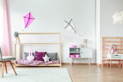 Pink decorations in kids bedroom. White and pink kite on wall in spacious kids bedroom with chair on carpet, pink decorations and toys stock photo