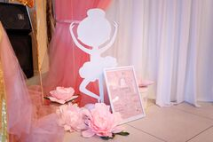 Pink decorative flowers, paper ballerina shape and baby girl metric with name Arina, date of birth, height and weight