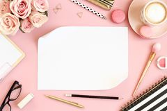 Pink desk table with flowers, cup of coffee and macarons. Desk with pink roses, pen, pencils, scissor, spiral notebook, empty paper, glasses, makeup brush and Royalty Free Stock Image