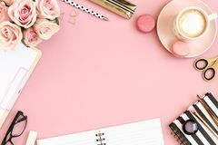 Pink desk table  with pink flowers, cup of coffee and macarons Stock Photos