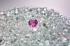 Pink diamonds are placed on a pile of white diamonds